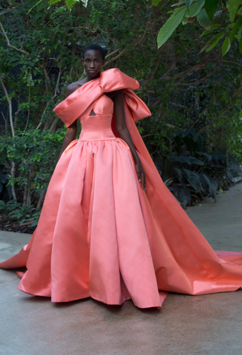 model with a coral dress made by Ashi in a garden