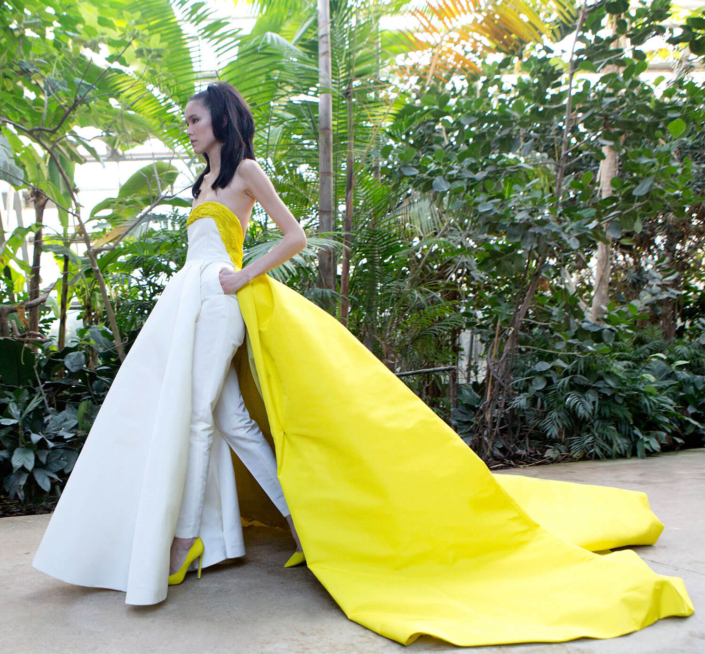 model with a white and yellow dress walking in a garden