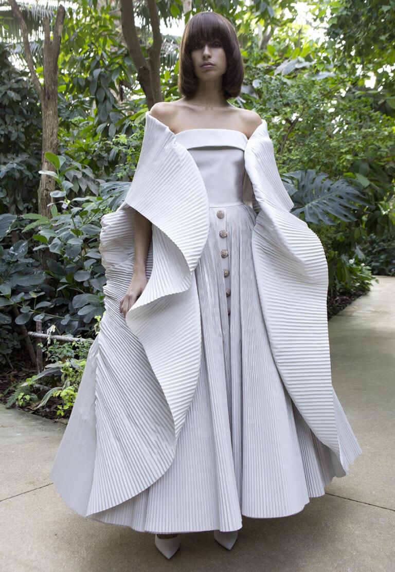 girl wears a white dress made by Ashi in a garden