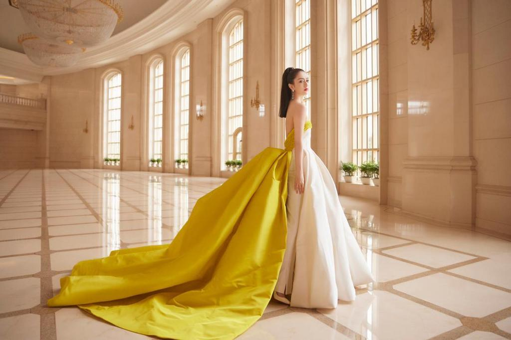 Tong Lo Ya wears a yellow and white dress made by Ashi